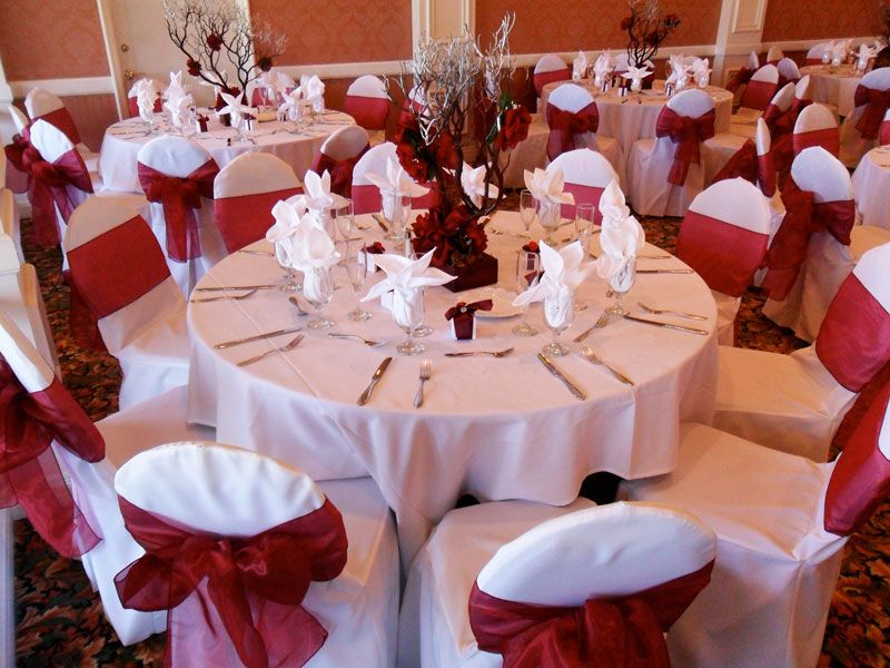 White Chair Covers Available For Rent With Candy Apple Red Bows In