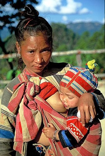 Northern Thailand    A Lisu hilltribe woman nursing her baby as she walks down the road. This photo cost me a banana!