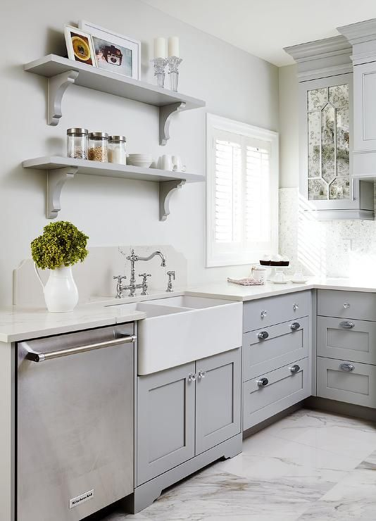 Beautiful gray kitchen features a dual farmhouse sink ...