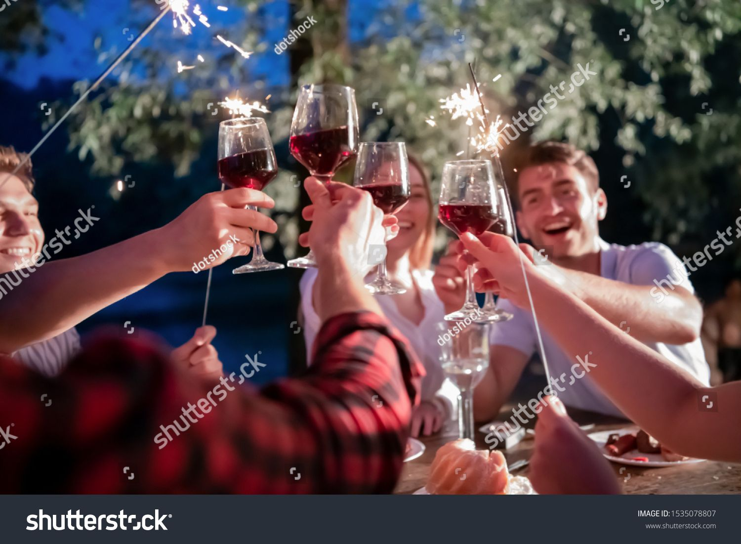 Group Of Happy Friends Celebrating Holiday Vacation Using Sprinklers And Drinking Red Wine While Having Picnic French In 2020 Happy Friends Holiday Vacations Vacation
