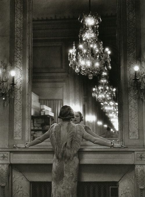 A model pauses to regard herself in the grand mirror of the Molyneux atelier, Paris, 1934