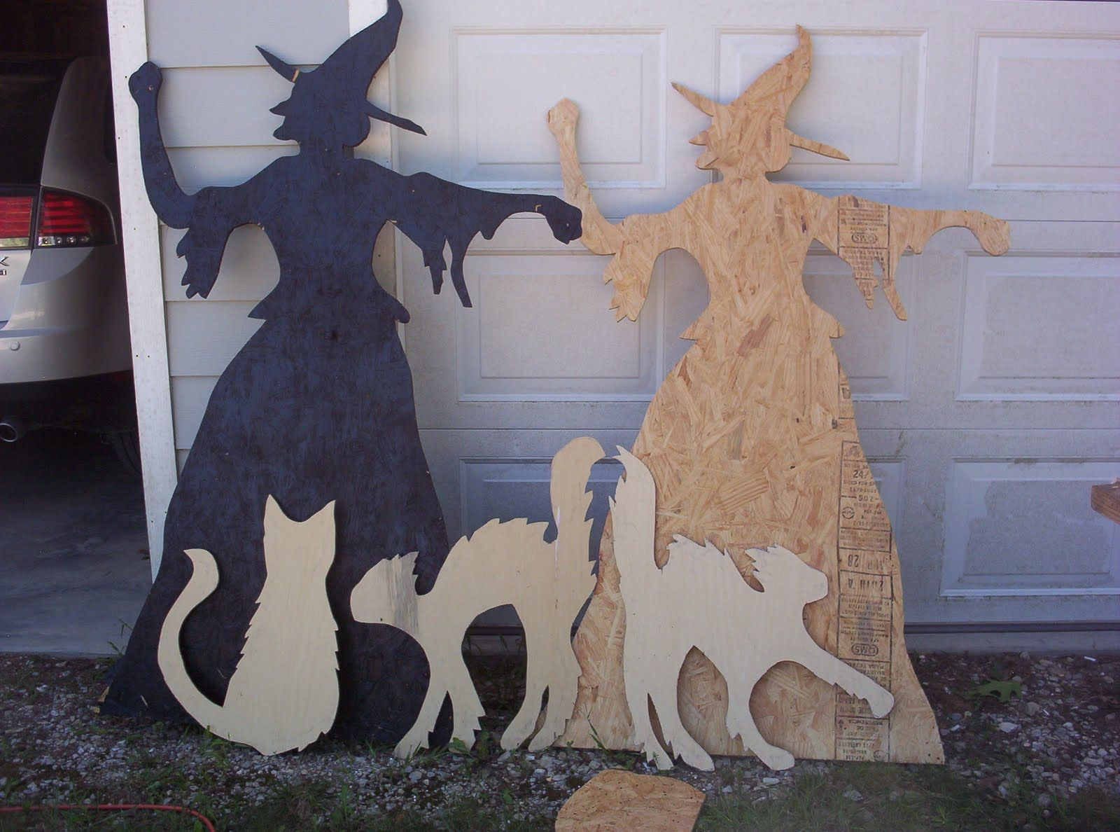 Halloween yard witch and catsi see a black paper cutout stuck to