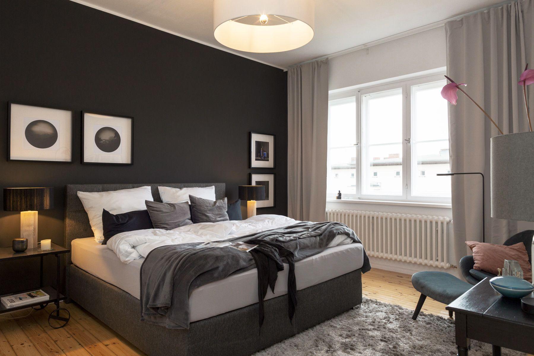 Schlafzimmer mit Boxspringbett und dunkelgrauer Wand in