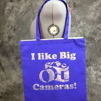 Hand painted blueberry bag with a I like big cameras! design on it. Design is painted in silver on one side only. Perfect for Photographers, conventions, trips to the comic shop, as a reusable shopping bag or as a purse.  Blueberry (Blueish purple) 100% cotton canvas promo bag (thinner than reg...