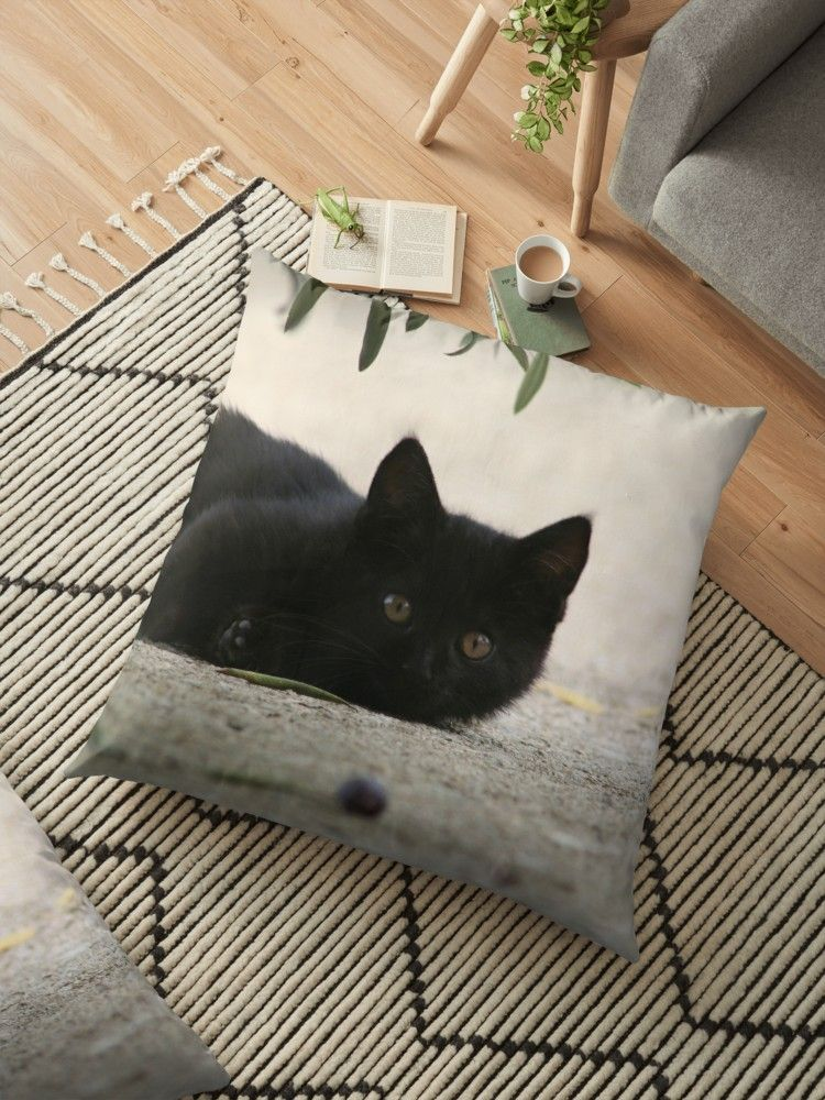 'Black Kitten Playing with Black Olives' Floor Pillow by