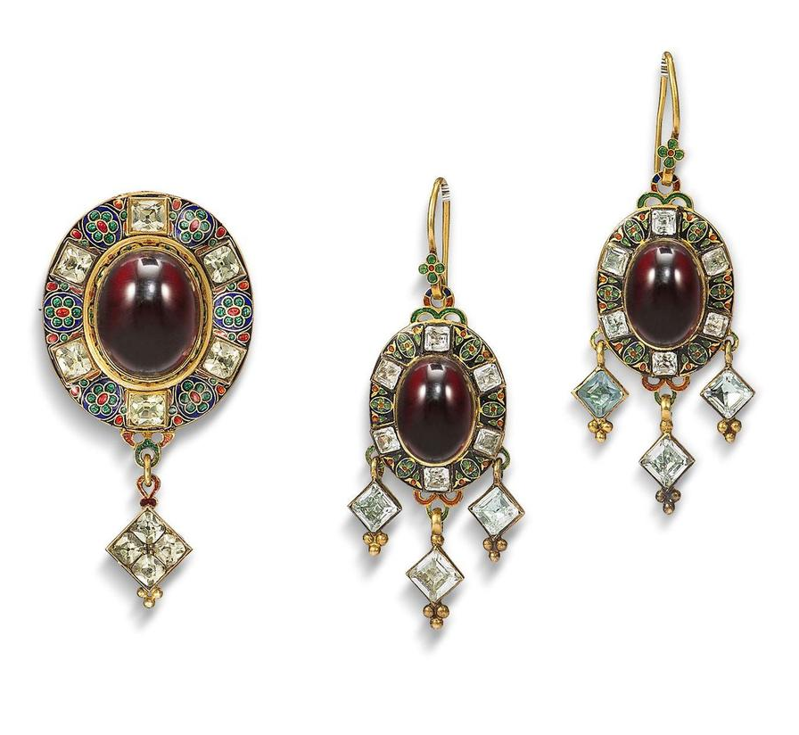 A Holbeinesque brooch and earring suite, circa 1865 -  The brooch set to the centre with a cabochon garnet, within a champlevé enamel border in shades of blue, green and red and six cushion-shaped chrysoberyls, terminating in a lozenge-shaped chrysoberyl drop, mounted in gold, the reverse with glazed compartment and engraved foliate motifs, converted from a pendant, accompanied by a matching pair of earrings.  | © Bonhams 2001-2014