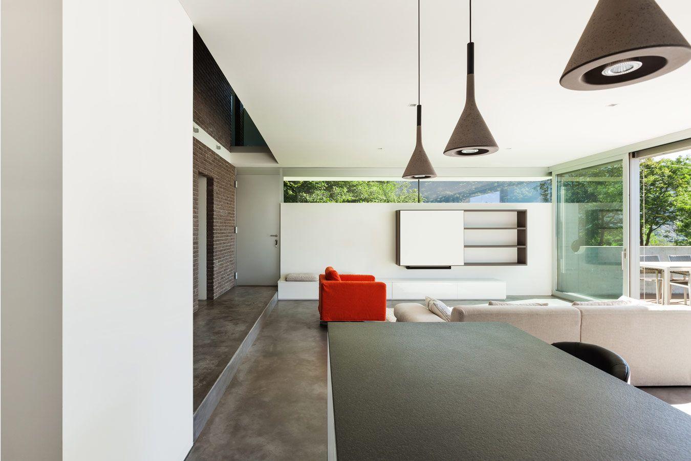 Woonkamer met betonvloer en grote ramen  interieur