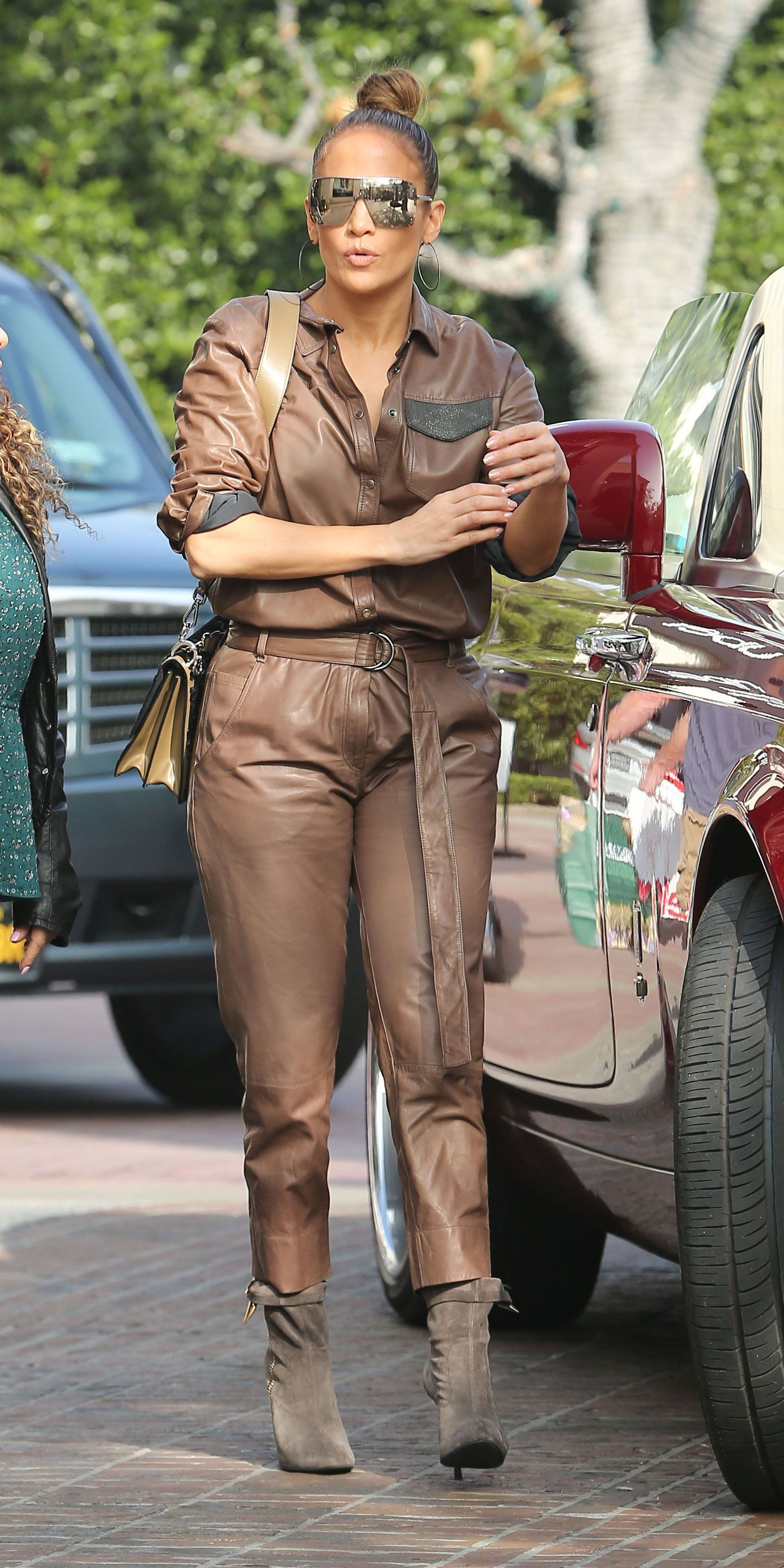 c1367b10a4f1 Jennifer Lopez put a glamorous twist on the boiler suit trend by wearing a  luxurious leather design by Brunello Cucinelli. Her Chanel shield  sunglasses