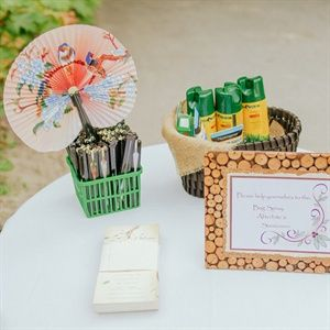 A Little Table Set Up With Water Sunscreen Bug Spray Fans Sungles
