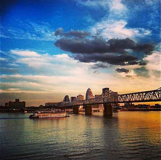 Belle of Louisville in front of the Louisville skyline at sunset.