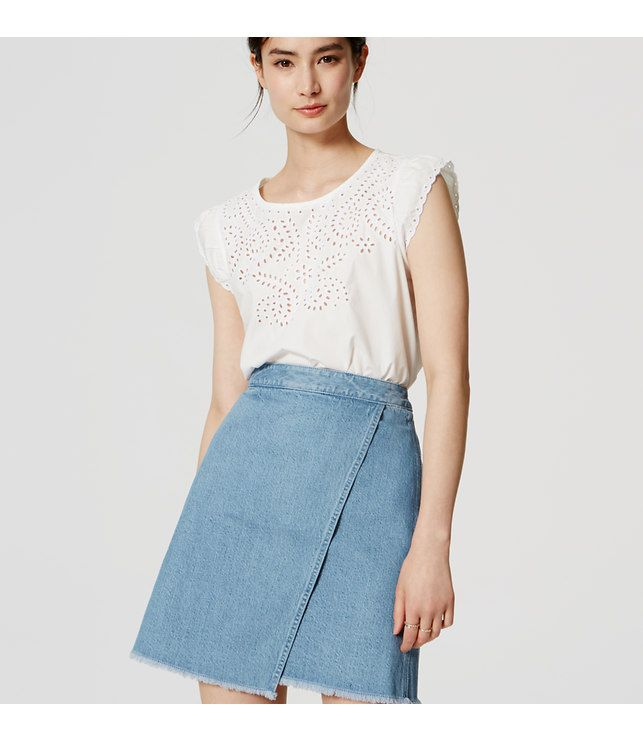 "The tried-and-true denim skirt takes a chic turn in the form of this modern wrap style. Asymmetric wrap front. Frayed hem. Exposed back zip. 17 1/2"" long."