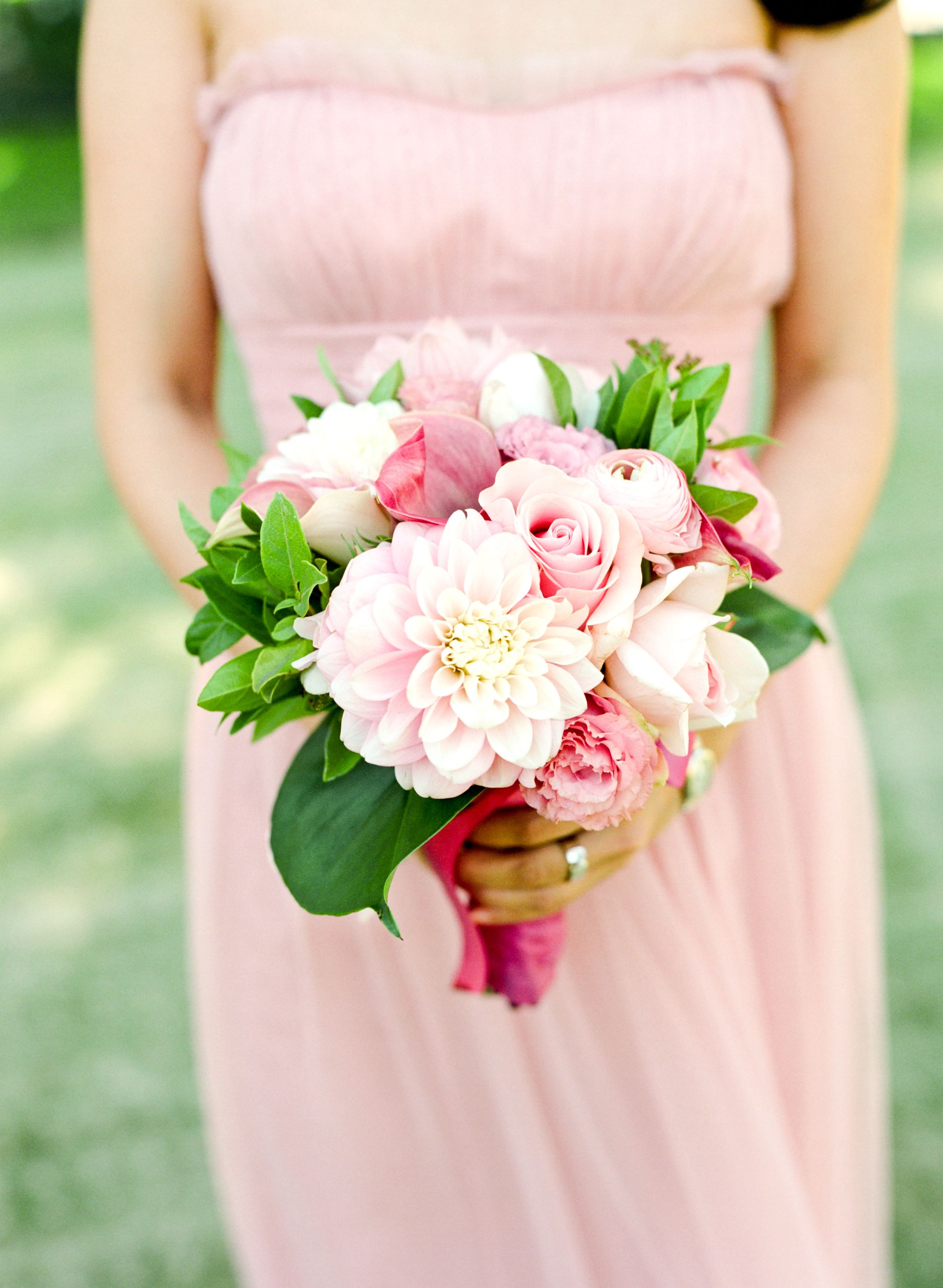 Beautiful pink bridesmaid bouquet of dahlias, calla lilies, ranunculus and roses.