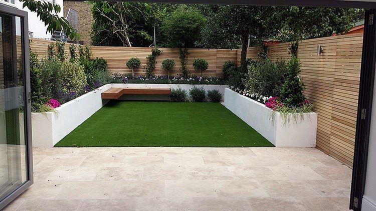 Kunstrasenteppich und hochbeete mit pflanzen im kleinen hinterhof ...