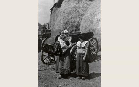 Twee meisjes en een jongen in streekdracht uit Bunschoten-Spakenburg. De jongen is gekleed in een jurkje met schortje. Deze dracht wordt gedragen tot het vierde jaar. Het rechter meisje is rond de 12 jaar. Ze draagt reeds de lijfkleding van de oudere meisjes en vrouwen, maar heeft op haar hoofd nog de 'pluummuts' (meisjesmuts). Het linker meisje is rond de 14 jaar of ouder. Zij draagt reeds de zwarte ondermuts en gehaakte tussenmuts. 1918-1941 vanAgtmaal #Utrecht #Spakenburg