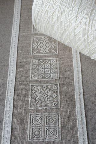 Inspiration, cream thread on dark linen