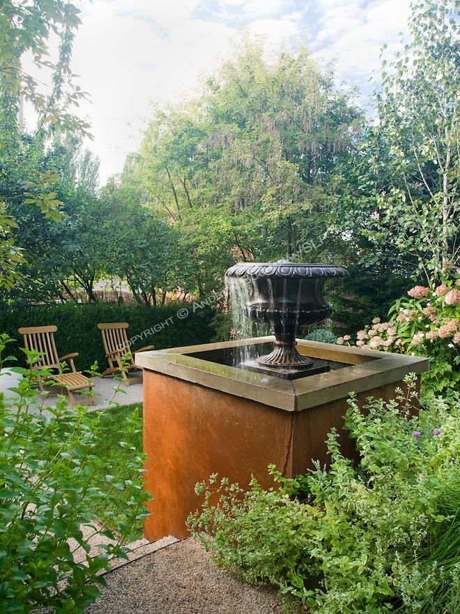 a water feature set among lush mixed beds serves as a focal point