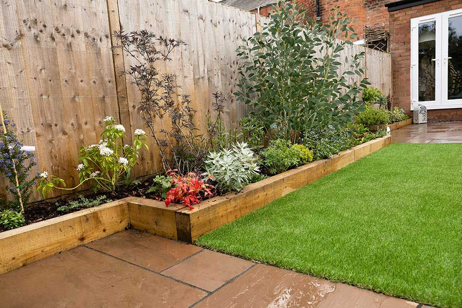 The raised sleeper beds work perfectly in this low maintenance garden. #flowerbeds
