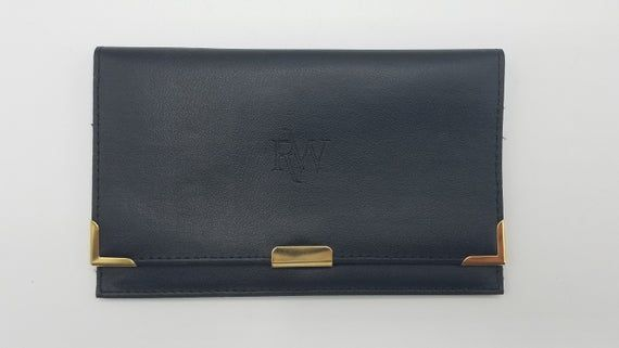 Listed is a Raymond Weil women's black leather wallet in unused, mint condition.  The wallet features an impressed RW logo with gold toned metal corner protectors and a snap closure,