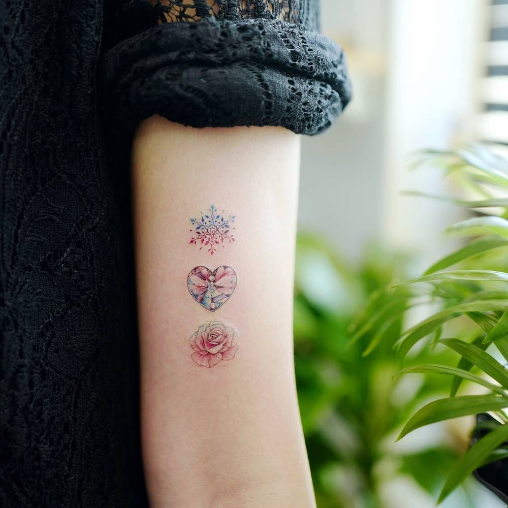 Snowflake, heart shaped gem and rose tattoo on the bicep.   tats ...