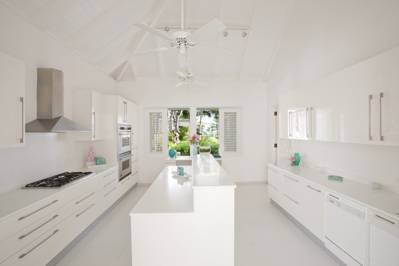 The cool all-white kitchen pulls all focus towards the tropical setting outside