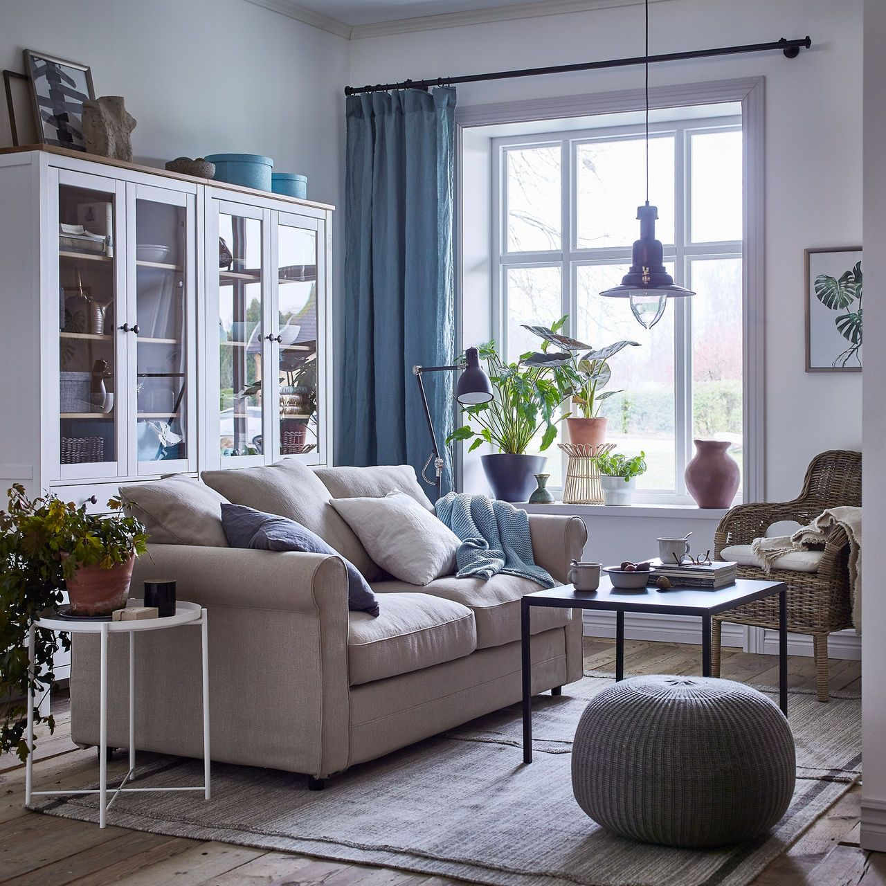 A cosy beige and white living room with blue curtains and a grönlid 2 seat sofa in sporda natural beside a rattan chair and glass storage cabinets