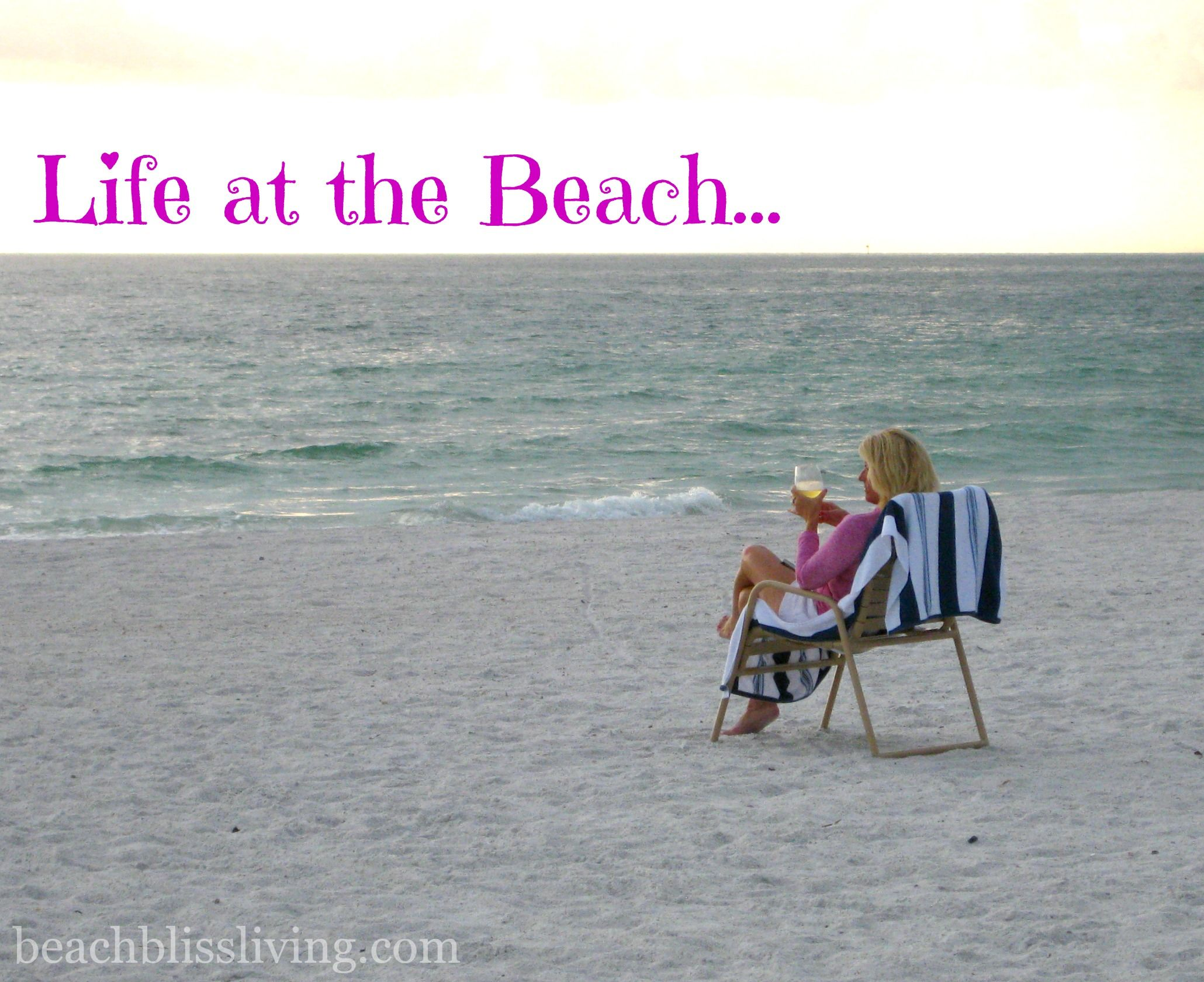 Woman sitting at the beach with drink in hand, enjoying the early evening hour. Photo by Maya of beachblissliving.com