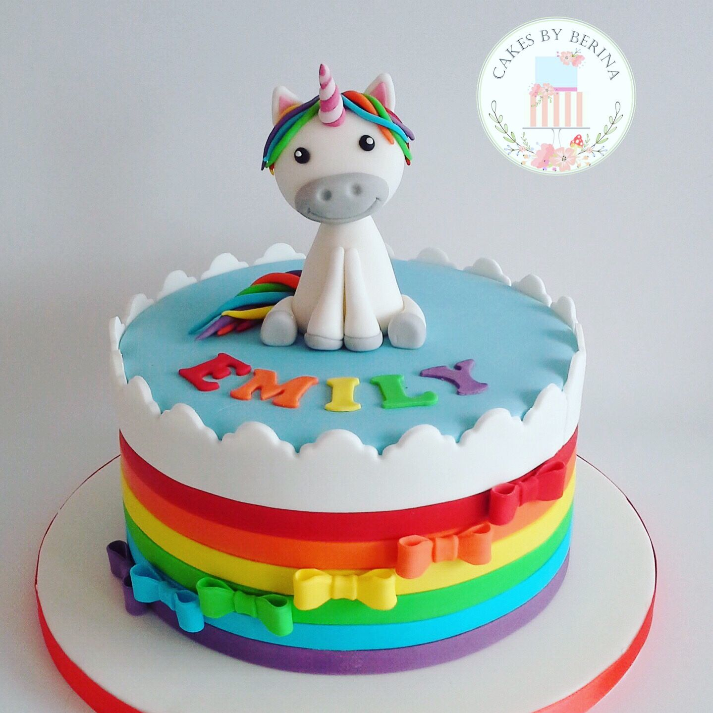 Bright rainbow cake with cute unicorn cake topper Designed by