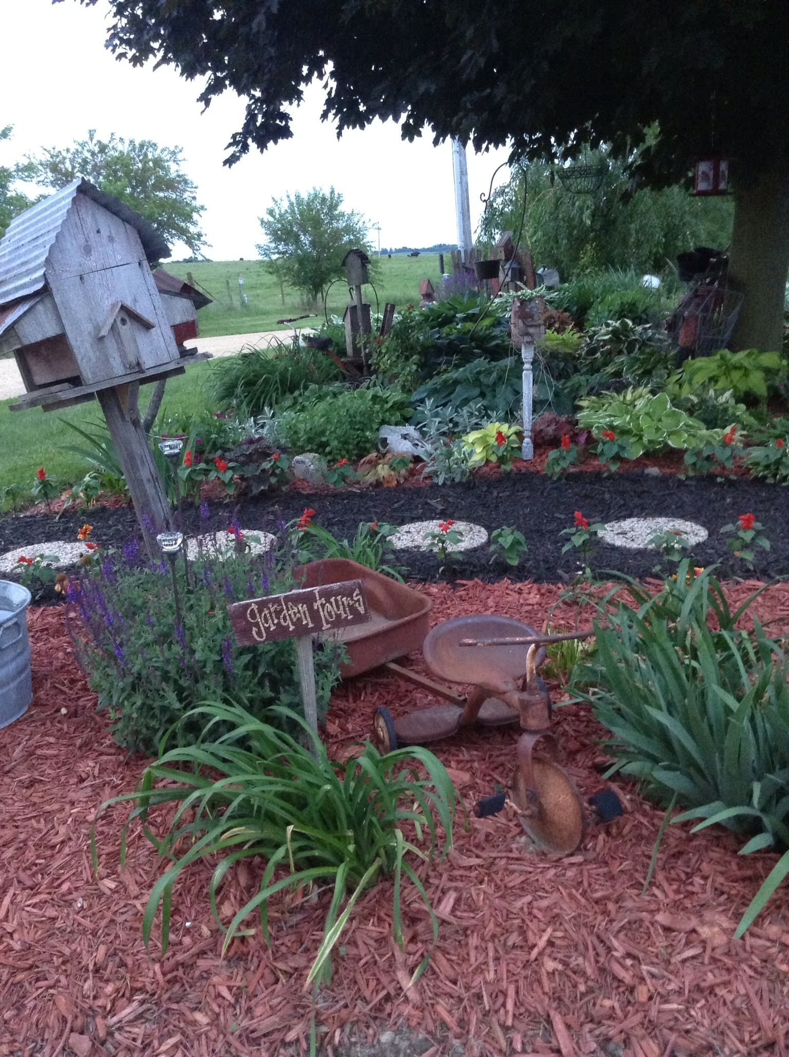 Stepping stone path with black mulch red mulch in the for Landscaping flower beds with stones
