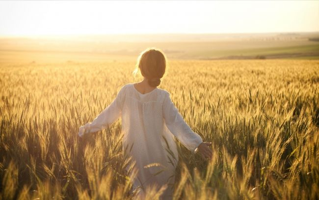 Wife standing nude in cornfield