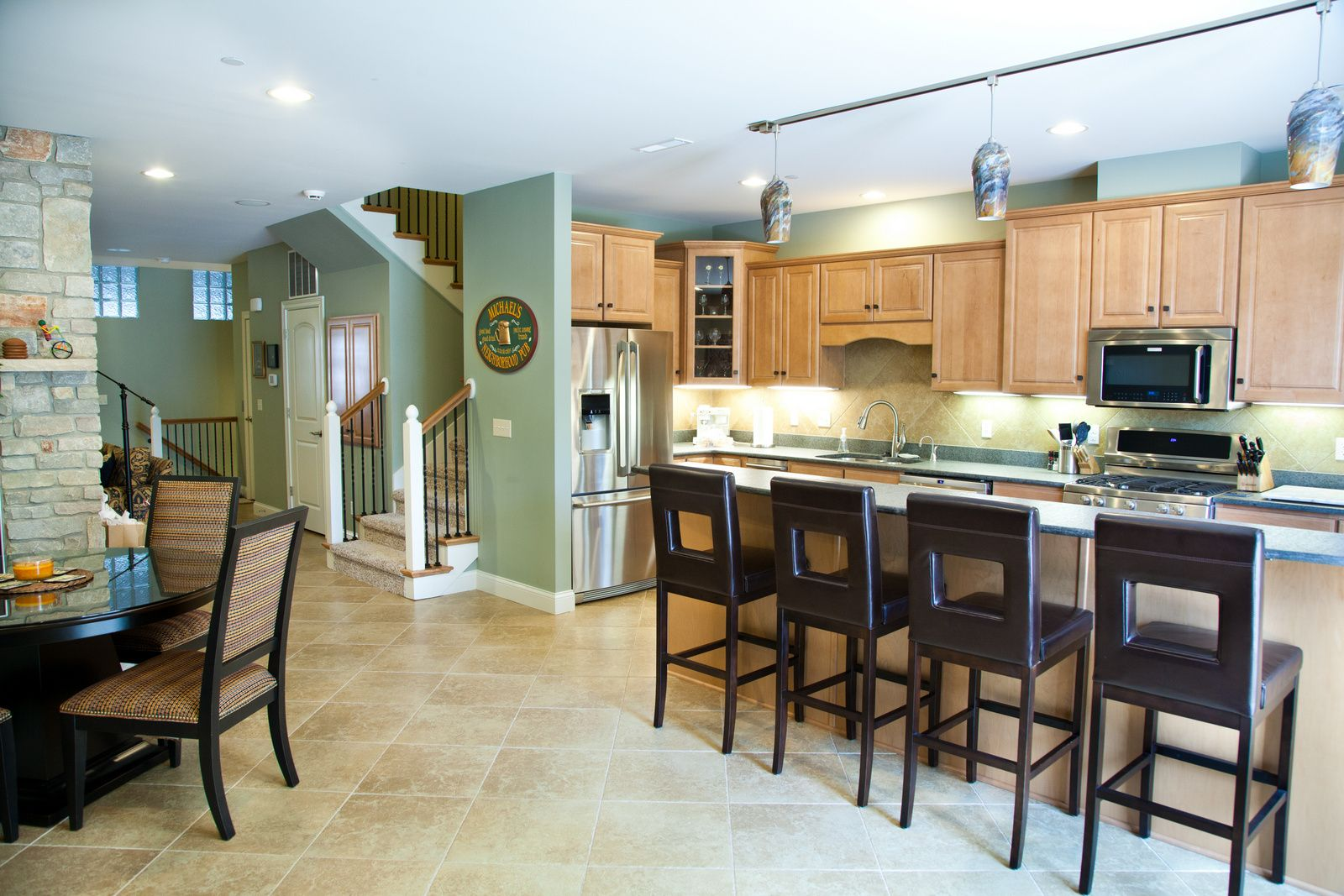 Ivy Quad Notre Dame Themed Condo Galley Kitchen With Porcelain Tile Floors Rustic Fireplace Maple Cabinet Kitchen Flooring Maple Cabinets Kitchen Remodel