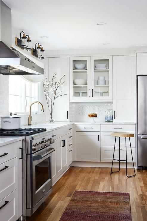 White and gray mosaic kitchen accent tiles are surrounded ...