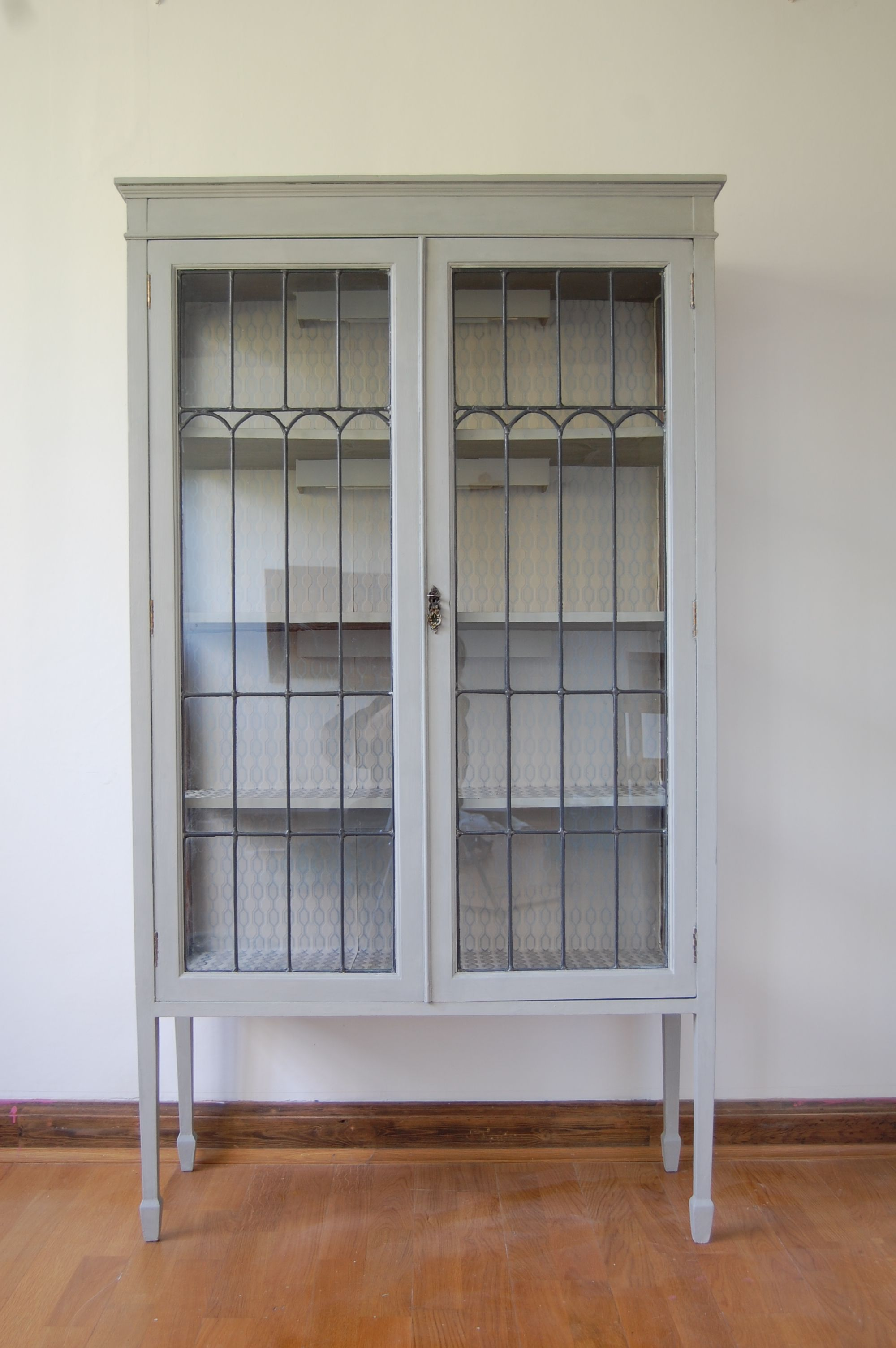 White Painted Wooden Display Cabinet Come With Clear Glass Door And Also Black Metal Frame Inside For Living Room Design
