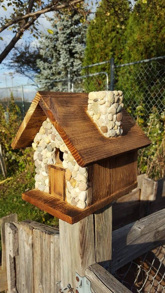 Birdhouse with stones covering front side and chimney