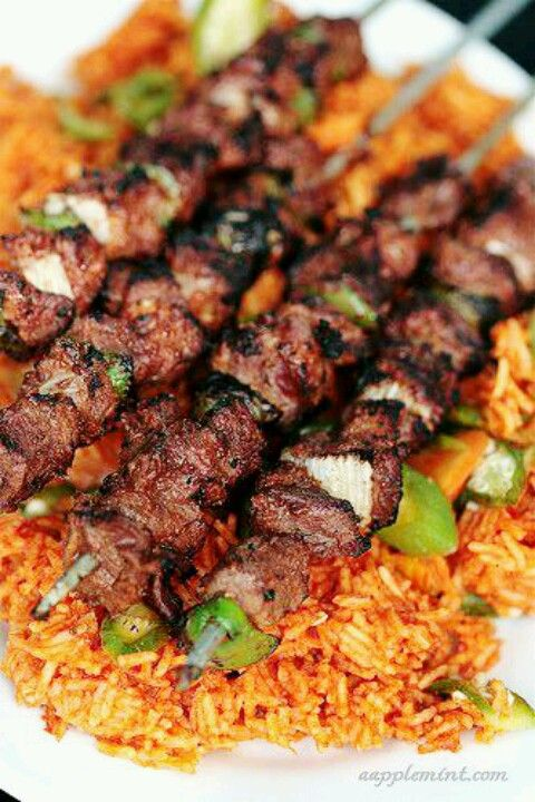 Spicy jollof rice served with goat cow meat kibabs for African cuisine restaurant