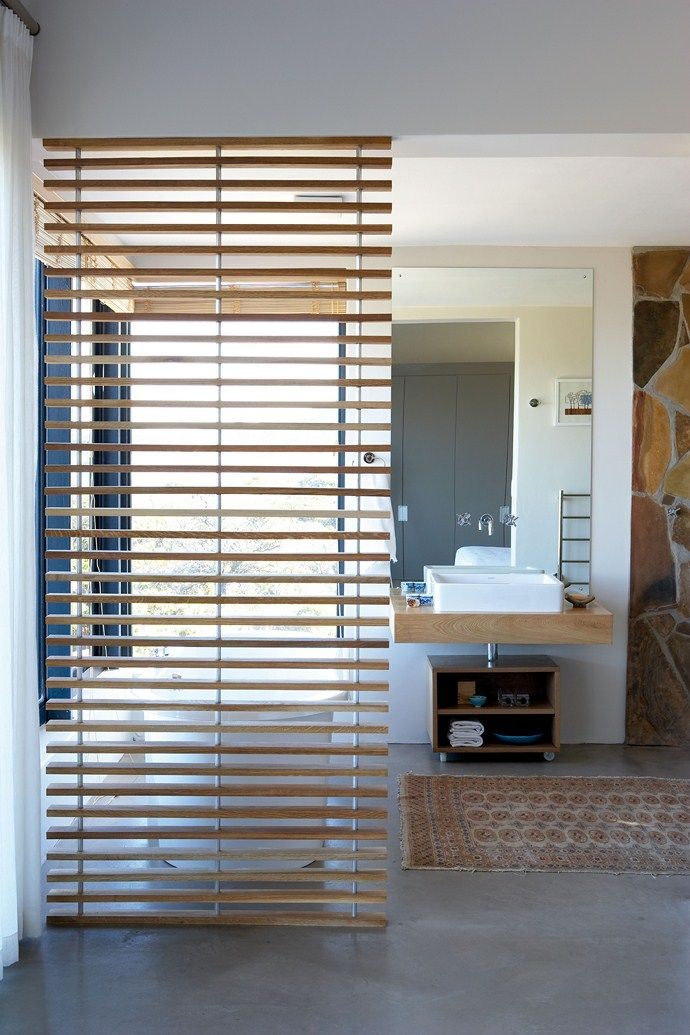 The slatted wooden room divider in the bathroom in the honeymoon