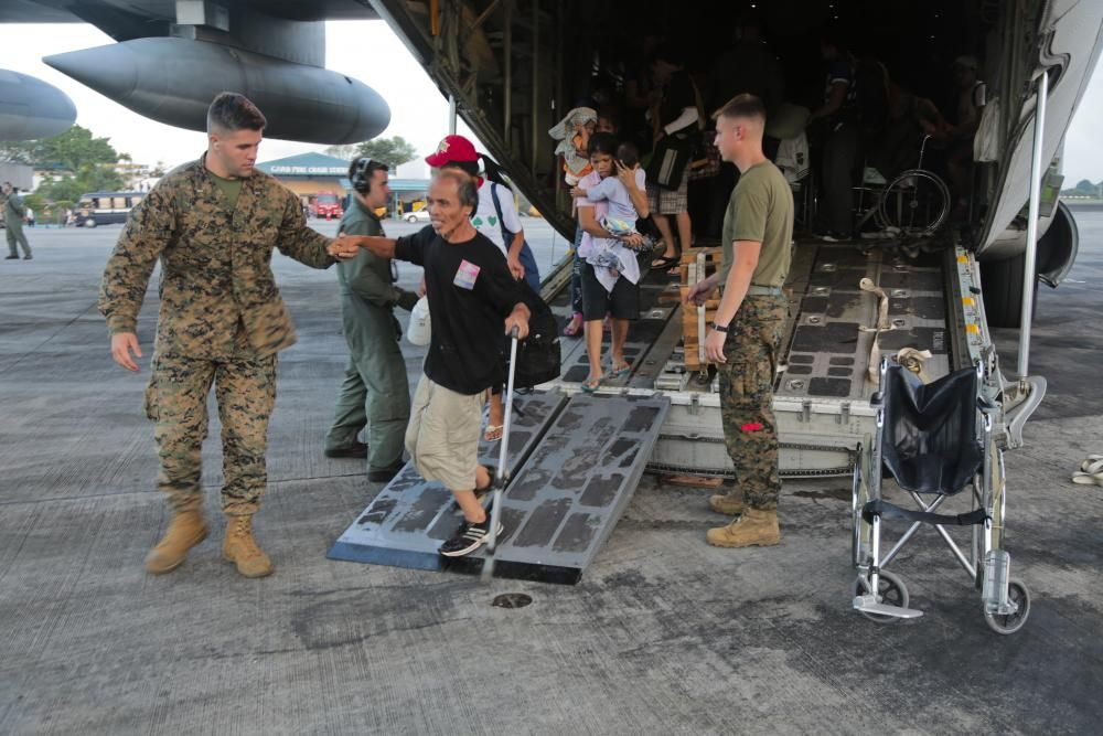 U.S. Marines with 3d Marine Expeditionary Brigade assist personnel displaced by Typhoon Haiyan off a KC-130J Super Hercules and toward the terminal at Villamor Air Base, Nov. 12. Marines and sailors with 3d MEB are supporting the Philippine Armed Forces in providing humanitarian assistance and disaster relief to affected areas throughout the Republic of the Philippines following the aftermath of Typhoon Haiyan. (U.S. Marine Corps photo by Lance Cpl. Caleb Hoover/Released)