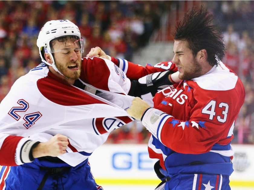 Jarred Tinordi #24 of the Montreal Canadiens and Tom Wilson #43 of the Washington Capitals exchange punches during the first period at Verizon Center on December 26, 2015 in Washington, DC.