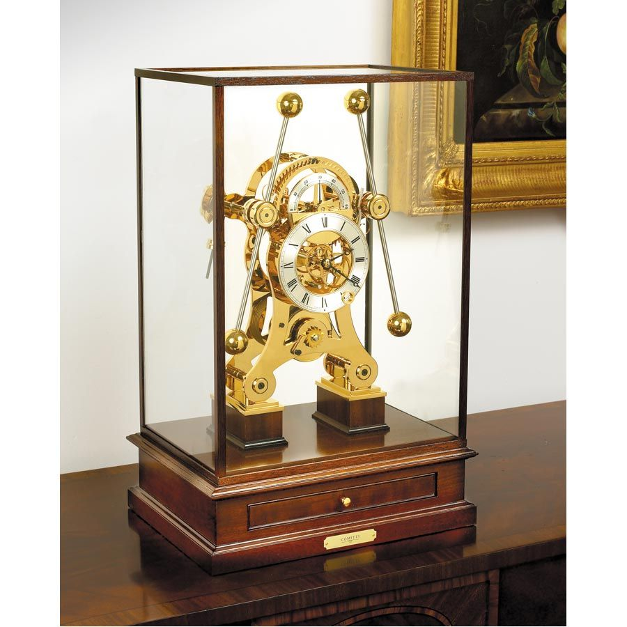"Grasshopper Clock. Based on the first marine chronometer made by the clock maker John Harrison (1693-1776), this extraordinary instrument features the ""grasshopper escapement"" operated by two inter-linked pendulums that compensated for the motion of a ship. Case is solid mahogany. Eight-day fusee movement is solid brass, hand polished and goldplated. Inside the drawer are a winding key and a paperback copy of Dava Sobel's ""Longitude"". $12,500"
