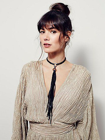 Leather Tassel Choker   Braided vegan leather choker featuring 18k gold plated loop accents and long fringe detailing. Adjustable lobster clasp closure for an easy fit.