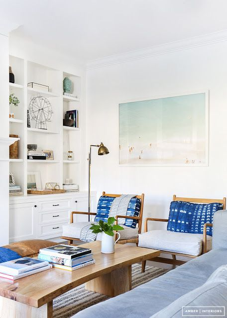 Crisp clean bohemian meets midcentury living room with vintage danish modern arm chairs indigo mudcloth pillows oversized beach print and floor to