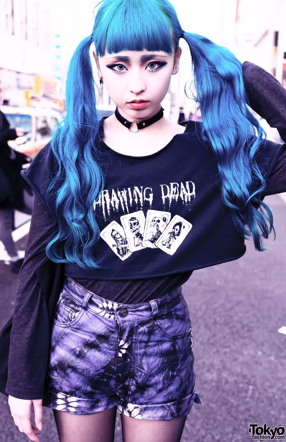 Blue hair, eyebrows, and eye contacts. Pigtails with straight across forehead bang and wavy ends. Leather choker with ring. Drawing Dead playing card cut black shirt with long sleeve underneath. High wasted shorts with floral grungy pattern and rolled up cuffs.View more photos at the source article.