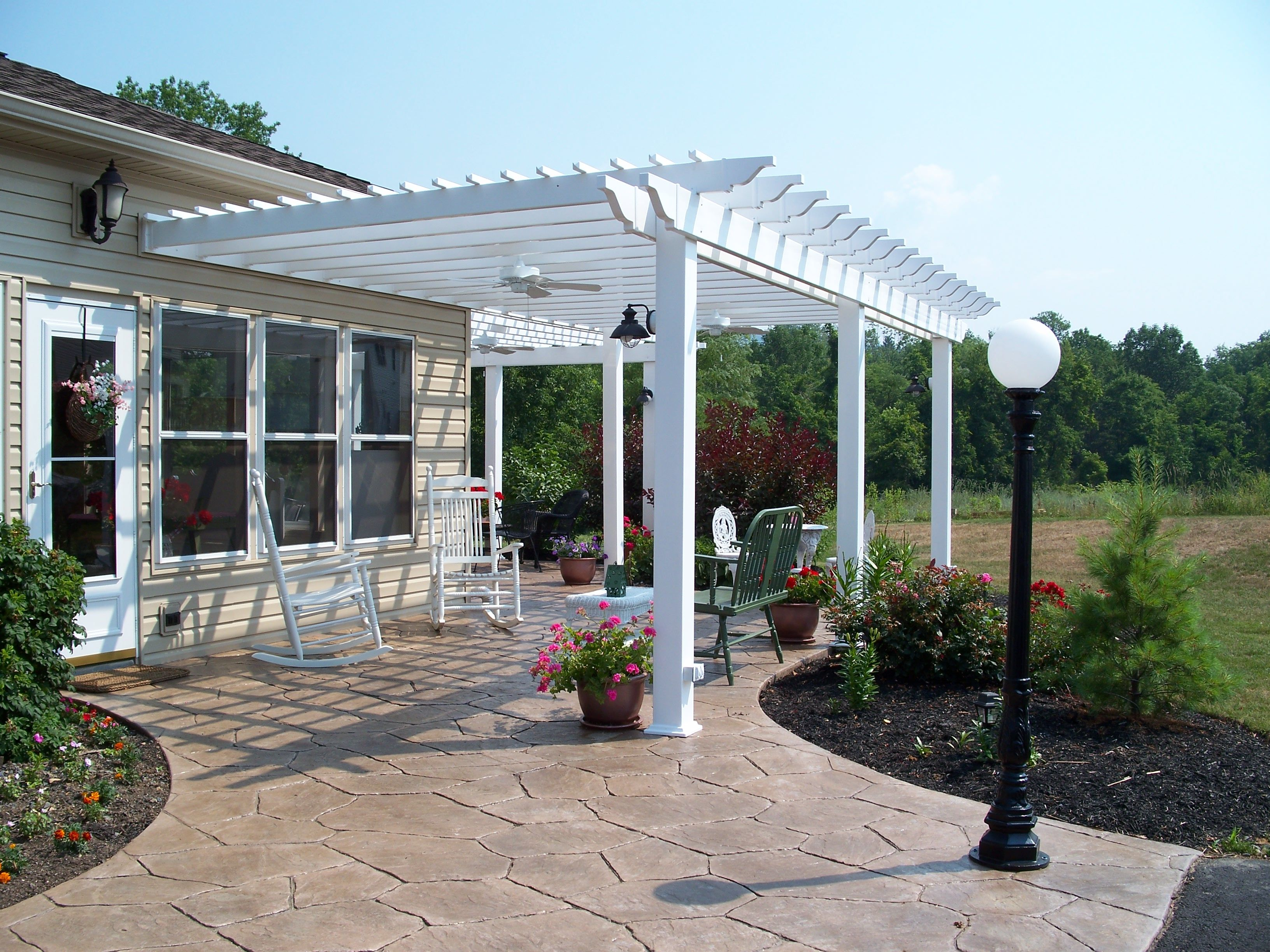 White Pergola Over Stamped Concrete Patio Design Ideas