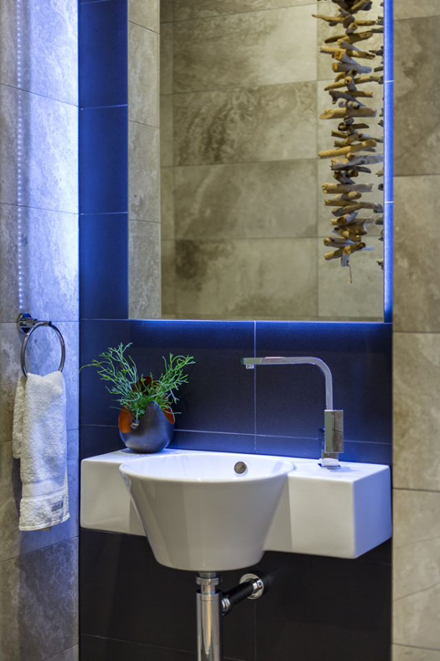 Silver travertine wall and floor tiles throughout add a touch of ...
