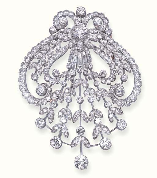 A DIAMOND AIGRETTE BROOCH   Designed as circular and baguette-cut diamond open floral and foliate panel with scrolled borders, mounted in platinum. Edwardian or Edwardian style.