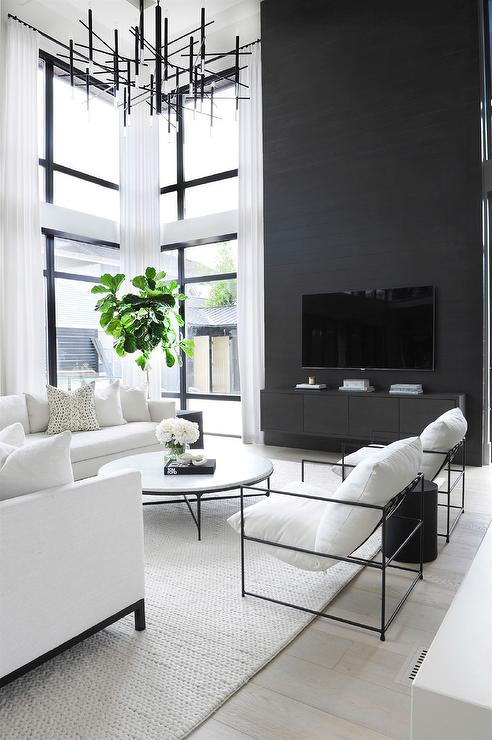 Two Story Black Accent Wall With Black Floating Tv Console Modern Living Room Modern White Living Room Black Living Room High Ceiling Living Room