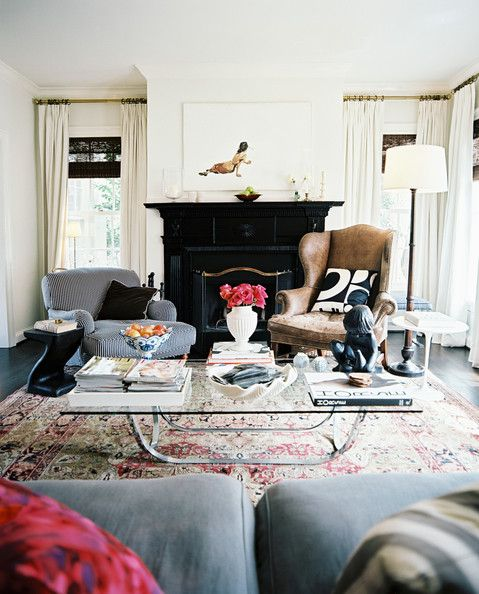 Black Fireplace Photo - A leather wingback, a roll-arm striped chair, and a glass-topped coffee table on a patterned rug