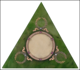 A fine Fabergé gold-mounted nephrite photo frame, workmaster Michael Perchin. Of triangular form with central circular aperture surrounded by gold mount with seed pearls interspersed with rubies in small square frames, each corner of the triangle with laurel leaf wreathes and ribbons each one studded with rose cut diamond.