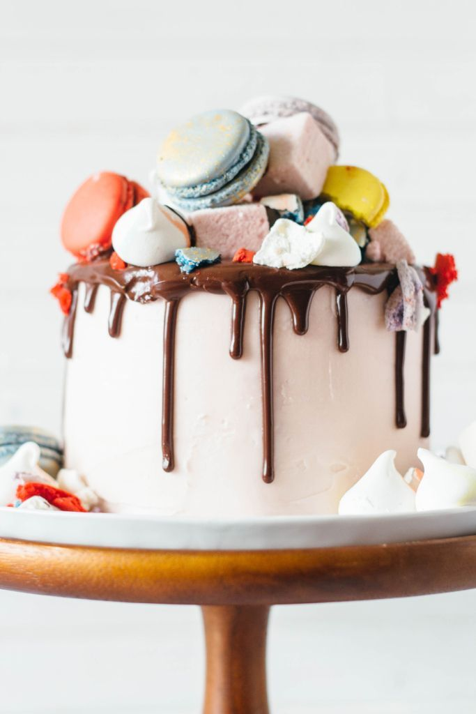 // cake topped with macarons, marshmallows, and meringues