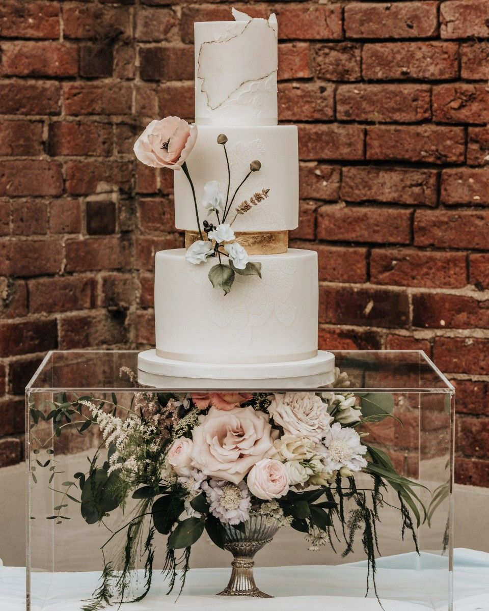 Bespoke prosecco and raspberry wedding cake on a perspex