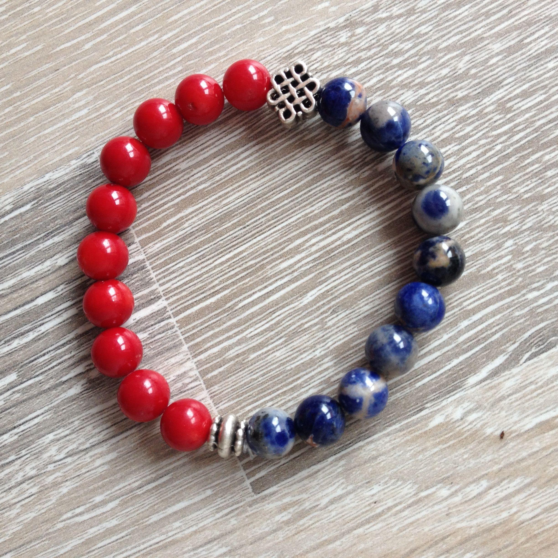 Armband van 8mm oranje sodaliet en rood bamboekoraal met metalen oneindige knoop en sierkraal. Van JuudsBoetiek, te bestellen op www.juudsboetiek.nl.